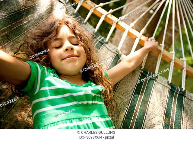 Young girl lying on hammock
