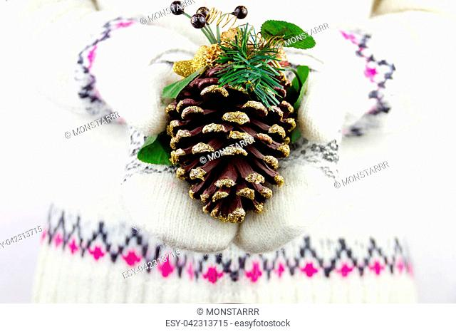Girl in mittens holding strobile decorated with branches from christmas tree