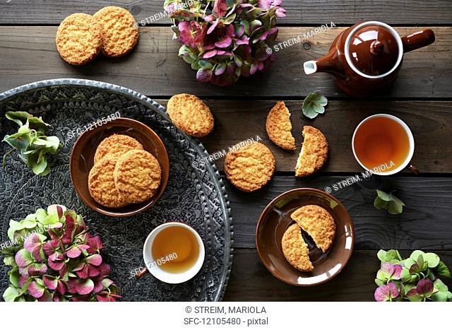 Coconut biscuits and tea on a tray, decorated with fresh flowers