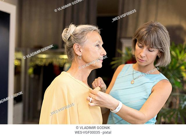 Shop assistant helping senior woman in a boutique