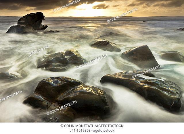 Sun sets beneath heavy cloud layer, seascape on rocks off Gillespie's Beach, Westland National Park, West Coast, South Island, New Zealand