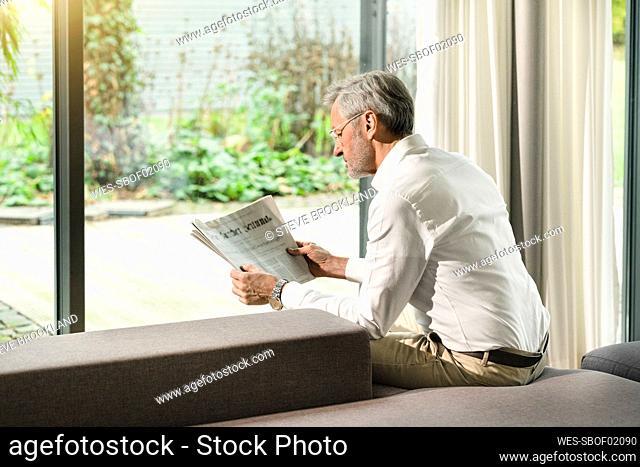 Senior man with grey hair in modern design living room reading newspaper