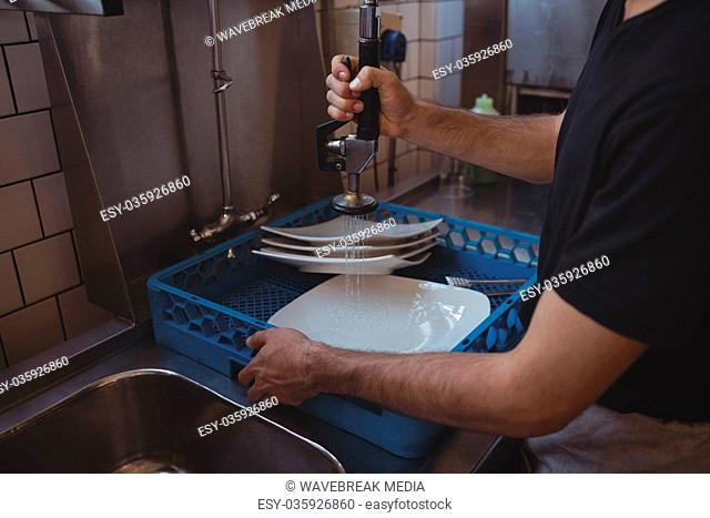 Mid section of washing plates at sink