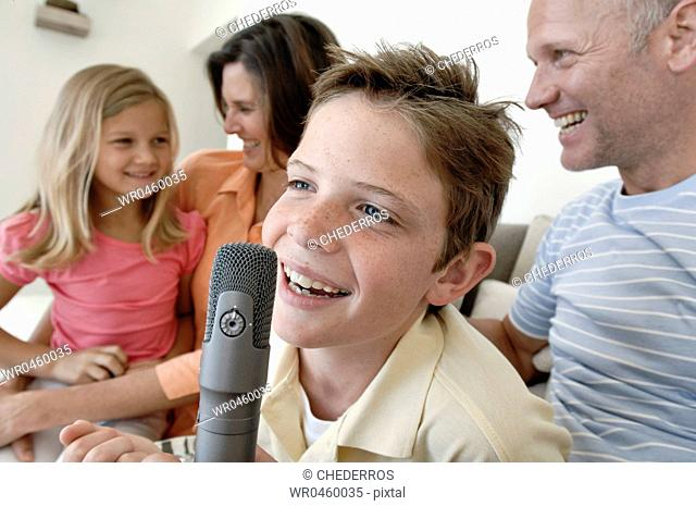 Close-up of a boy singing into a microphone with his family sitting beside him