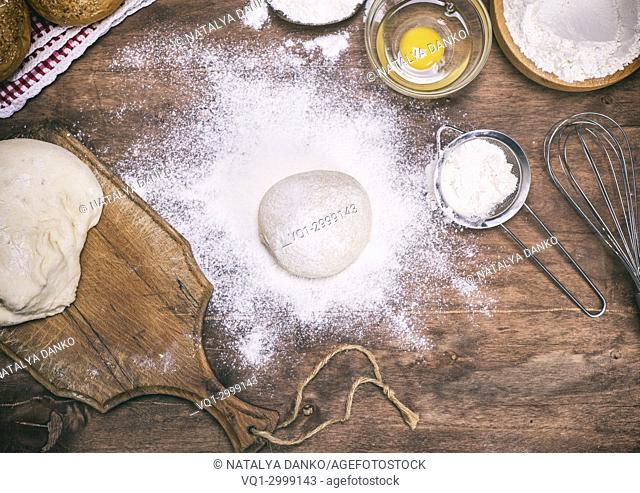scattered wheat flour on the table and raw yeast dough, ingredients for bread making