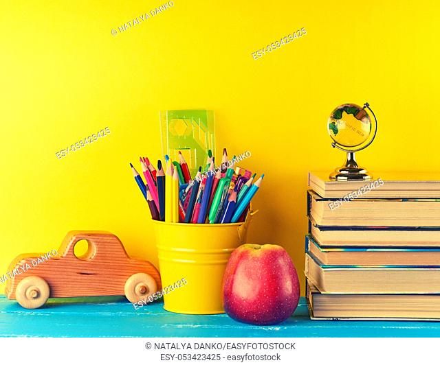 background back to school with children's stationery pencils, books, apple, glass globe on a blue background