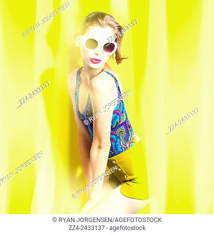 Attractive young retro woman wearing sunglasses on vibrant sunflared background. Beauty and fashion pinup girl