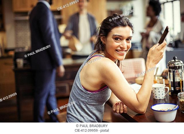 Portrait smiling young woman texting with smart phone at breakfast table