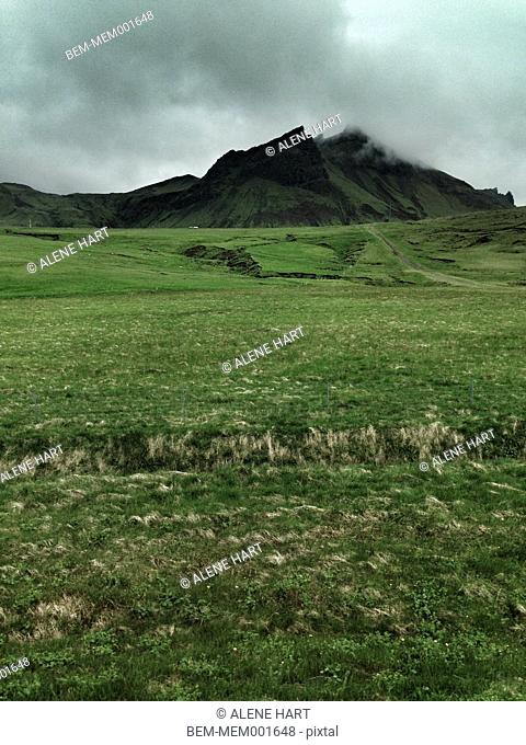 Grassy field and mountain in remote landscape