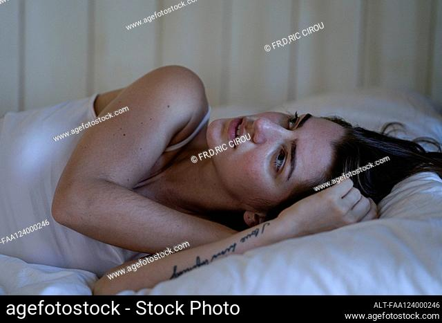 Sad young woman lying on bed