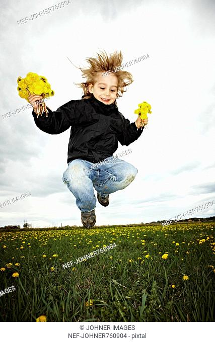 Boy jumping holding flowers in his hands, Sweden
