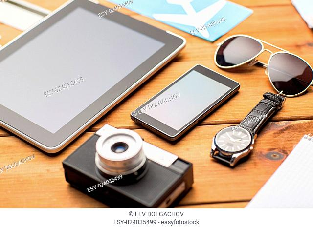 vacation, travel, tourism, technology and objects concept - close up of smartphone and personal stuff