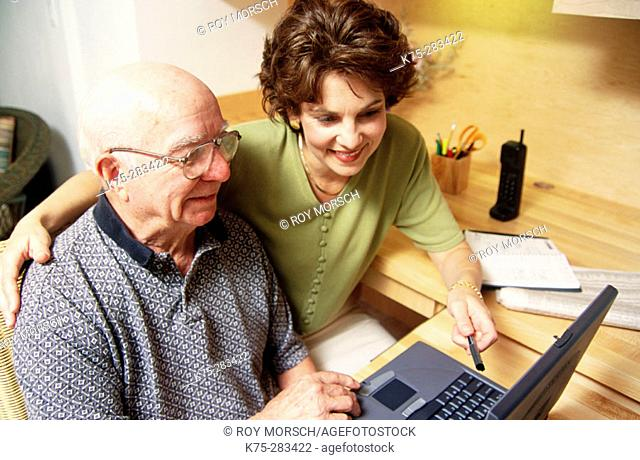 Daughter teaching senior to use computer