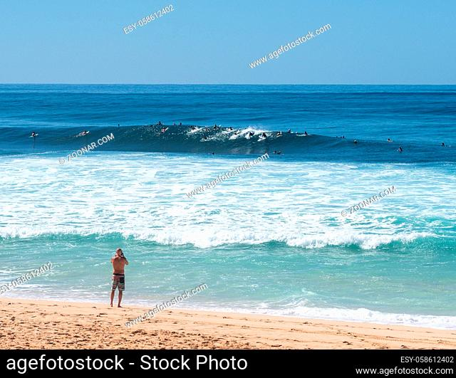 Many surfers waiting for big wave in the sea at Banzai Pipeline on north coast of Oahu, Hawaii