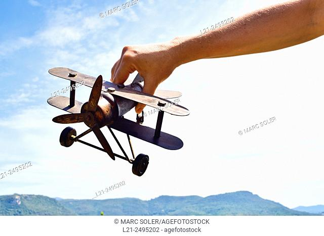 Close-up of  hand holding a model airplane against sky and mountain range