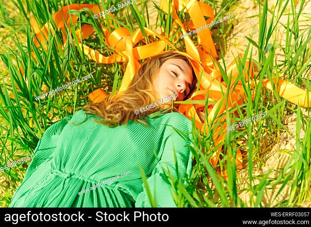 Young woman with closed eyes lying in a field with orange ribbons