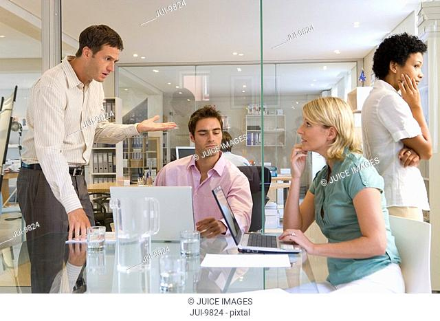 Small group of businessmen and women having meeting, man standing by colleagues using laptops at table