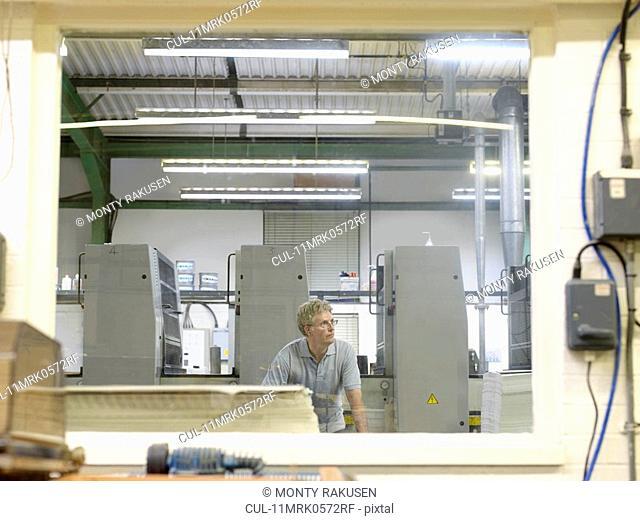Worker Inspecting Printers