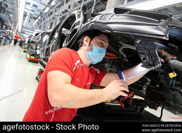 12 May 2020, Baden-Wuerttemberg, Stuttgart: An employee of Porsche AG wears a mouthguard in the production of the battery electric driven sports car Porsche...