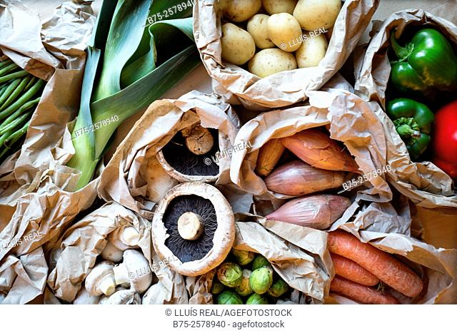 Close up of organic vegetables in paper bags. Mushrooms, Brussels sprouts, leeks, green beans, peppers, carrots, potatoes and shallots