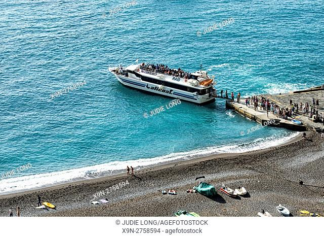 Positano, Amalfi Coast, Italy. People boarding and disembarking from a Ferry Boat at a pier on the beach
