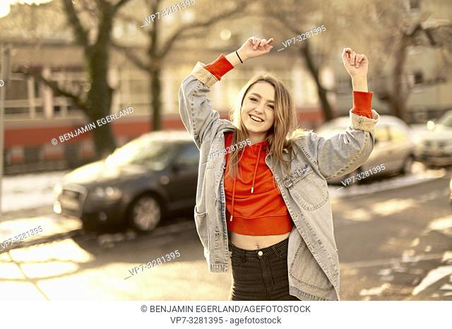young woman dancing on street in city, sunny winter, in Cottbus, Brandenburg, Germany