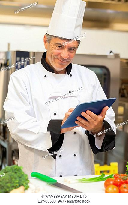 Chef using digital tablet and smiling in the kitchen