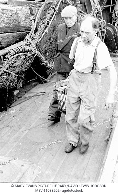 Life on a North Sea trawler -- two fishermen on deck, carrying a basket full of fish