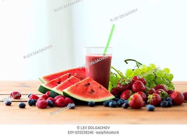 healthy eating, food, dieting and vegetarian concept - glass with fruit and berry juice or smoothie on wooden table
