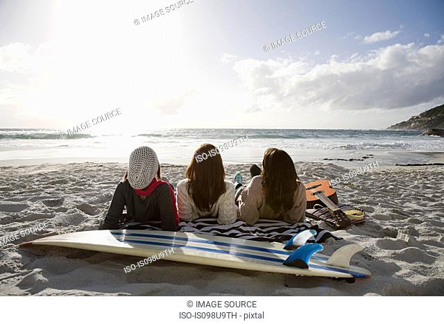Three girls lying on beach with surfboard