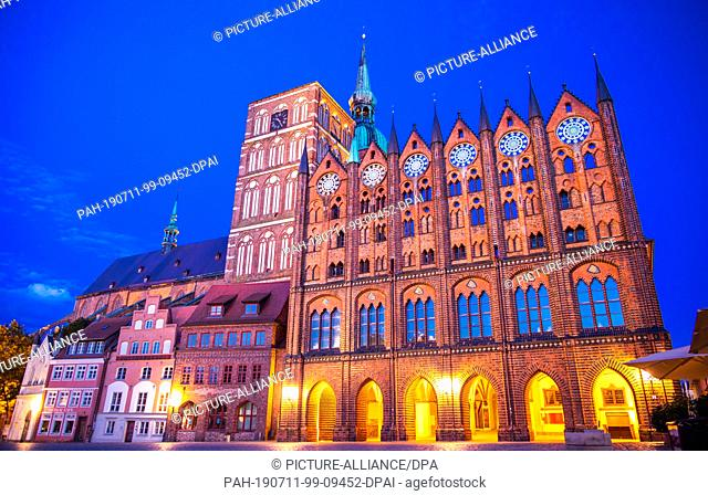 10 July 2019, Mecklenburg-Western Pomerania, Stralsund: The town hall (r) of Stralsund and the St. Nikolaikirche can be seen during the so-called blue hour at...