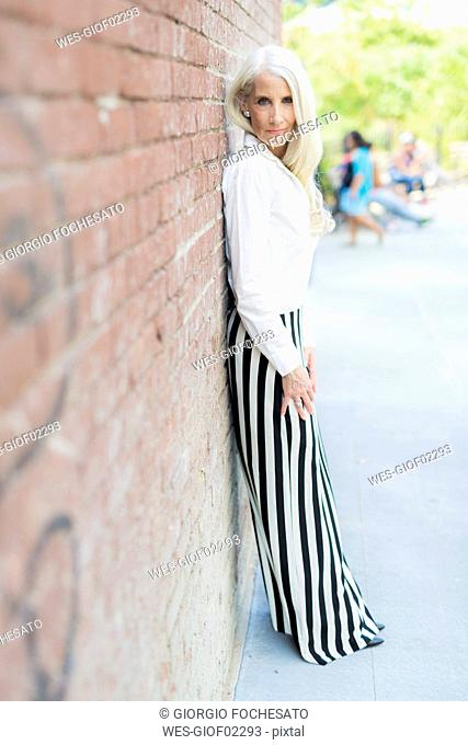 Portrait of mature woman leaning against brick wall