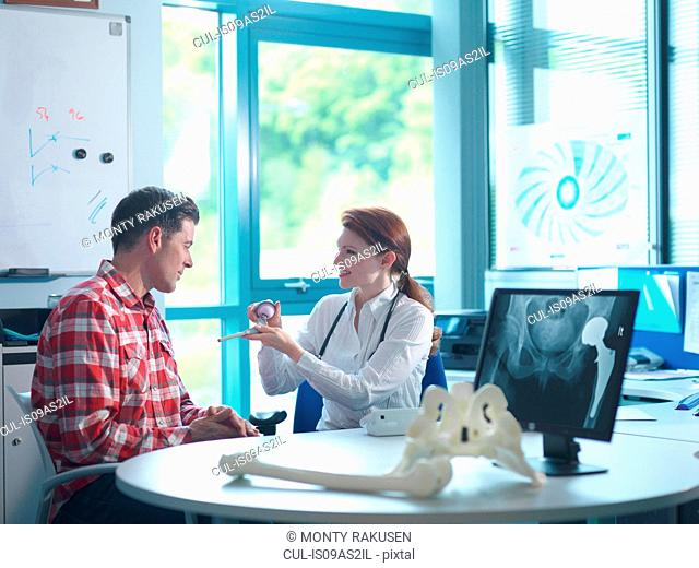Female orthopaedic consultant with patient in consulting room