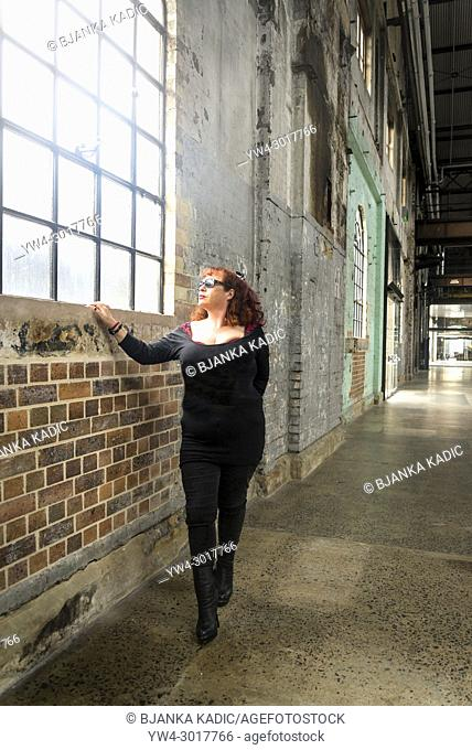 Woman dressed in black looking through a window in an industrial type of building