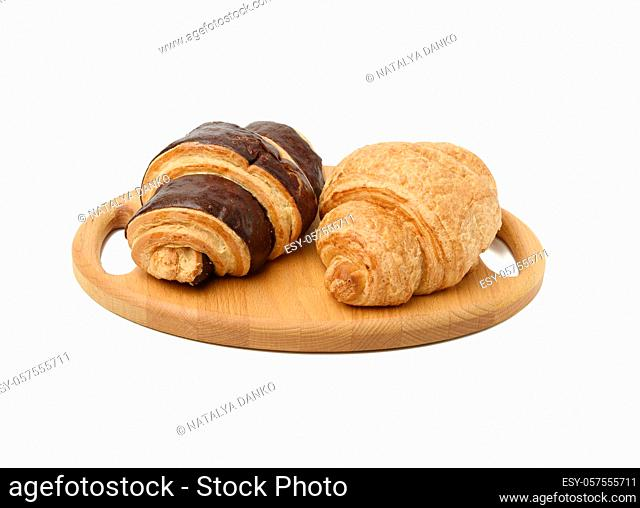 two baked croissants lie on a wooden tray, food isolated on white background, top view