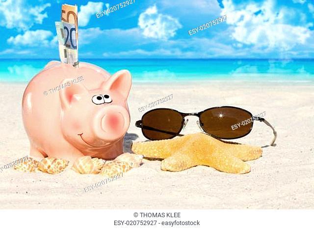 Sparschwein mit Geldscheinen und Sonnenbrille am Strand
