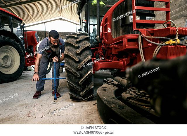 Mechanic changing tractor tyre