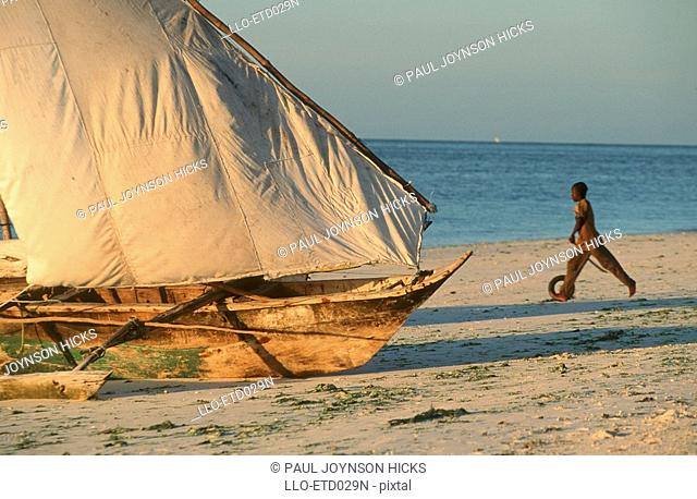 Boy Playing Next to Ngalawa Boat  Nungwi Beach, Zanzibar Island, Tanzania