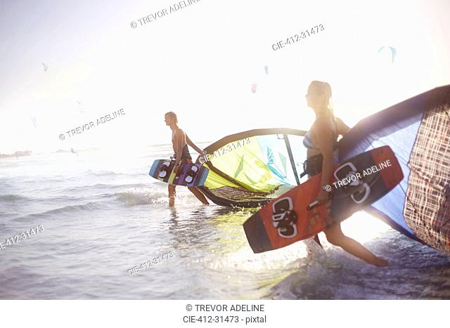 Couple walking into surf with kiteboard equipment
