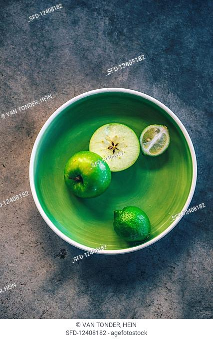 Half a green apple and limes in a green bowl