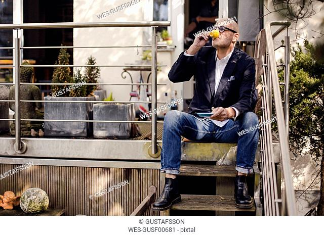 Senior man sitting on stairs of his patio, drinking coffee