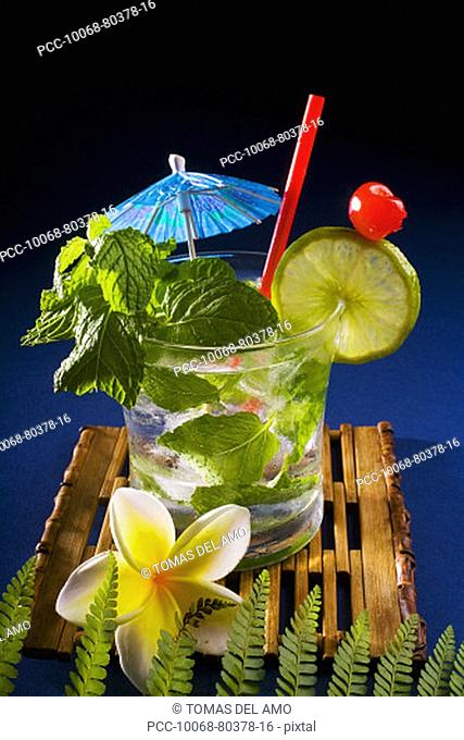 A mojito garnished with fruit and mint