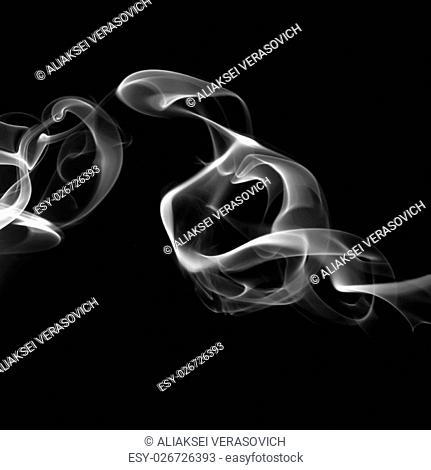 Abstract white smoke swirls on black background