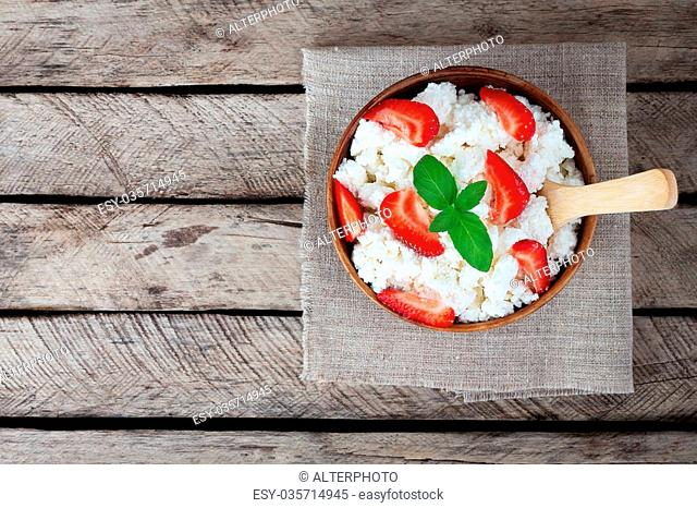 Bowl of cottage cheese, strawberry, wooden spoon on old wooden background. Healthy breakfast. Diet. Top view