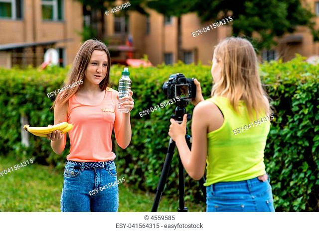 Two girls girlfriends, in the summer in the city. Record video on the camera. In the hands holding a banana bottle of water