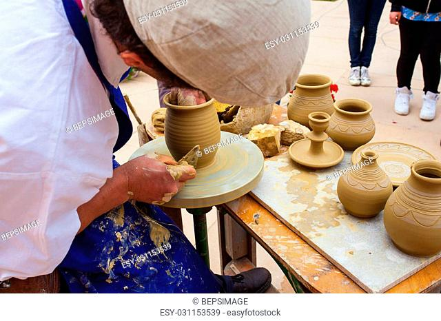 MILAN, ITALY - MAY, 20: Pottery maker uses a kick wheel to hand mold a pot from clay during the Expo, universal exposition on the theme Feeding the planet