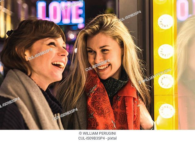 Two female friends looking in shop window