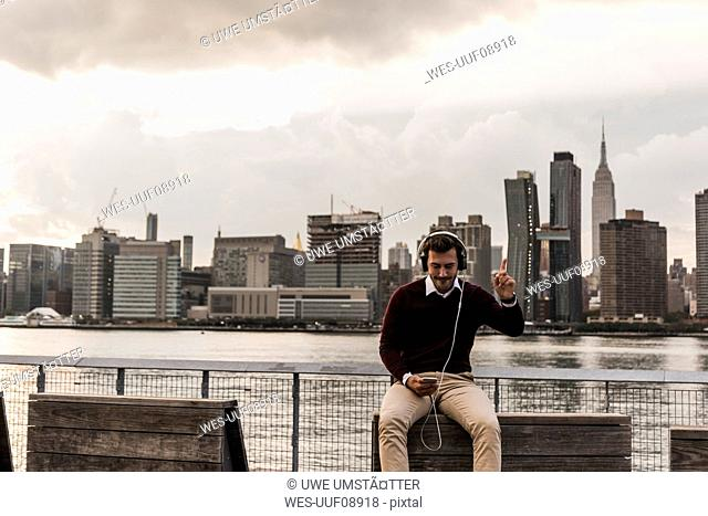 USA, New York City, young man with headphones and cell phone sitting at East River