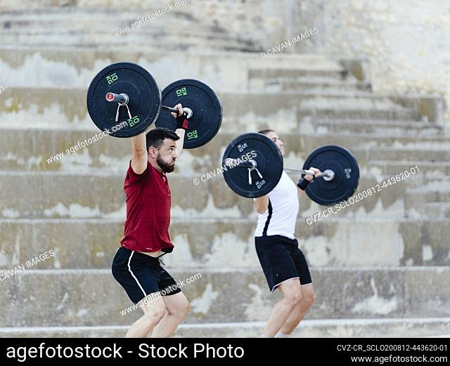 Two weightlifters lifting weights in an urban environment
