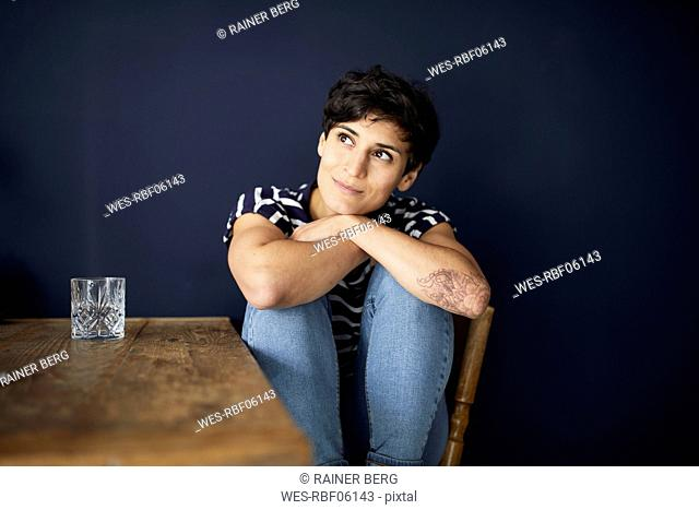 Portrait of woman at home sitting at wooden table